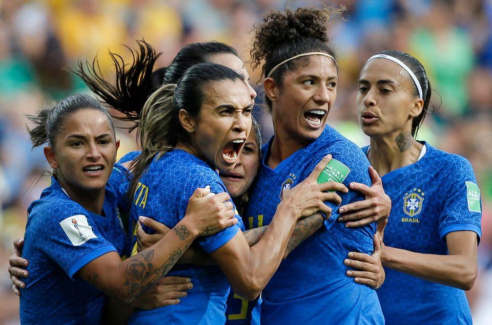 Marta (à esq.) celebra com suas companheiras de time após marcar um gol no jogo contra...
