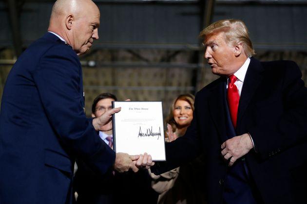 Le président Donald Trump serre la main du général Jay Raymond, après avoir...