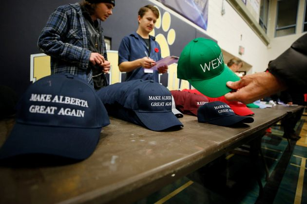A man buys a hat to raise funds at a rally for Wexit Alberta in Calgary on Nov. 16,