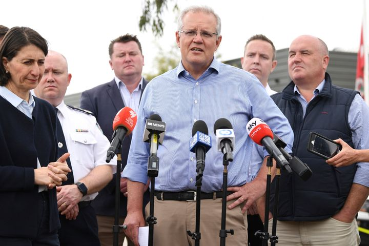 Australia's Prime Minister Scott Morrison, with NSW Premier Gladys Berejiklian, left, speaks to the media during a visit to the Wollondilly Emergency Control Centre in Sydney, Sunday, Dec. 22, 2019.