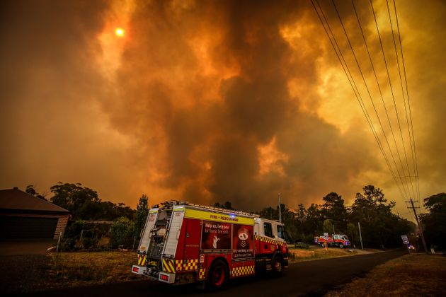 Firemen prepare as a bushfire approaches homes on the outskirts of the town of Bargo on December 21,...