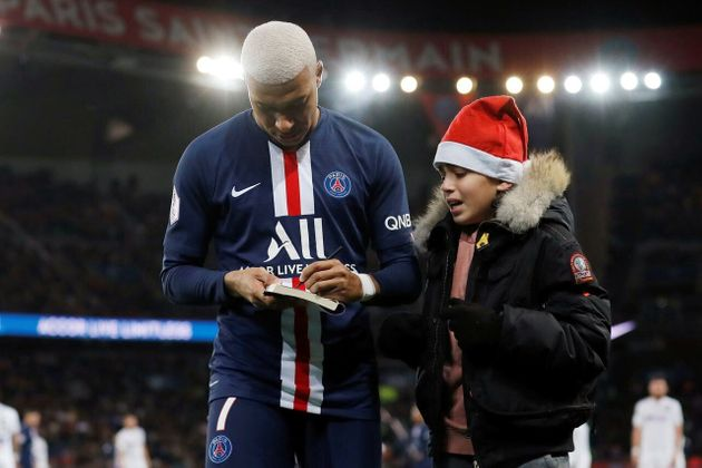 ピッチに乱入した少年が差し出した本にサインをするエムバペ選手