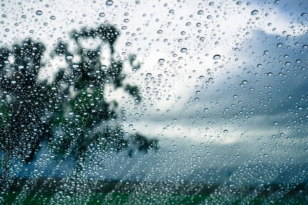 Drops of rain on the window; blurred trees and storm clouds in the