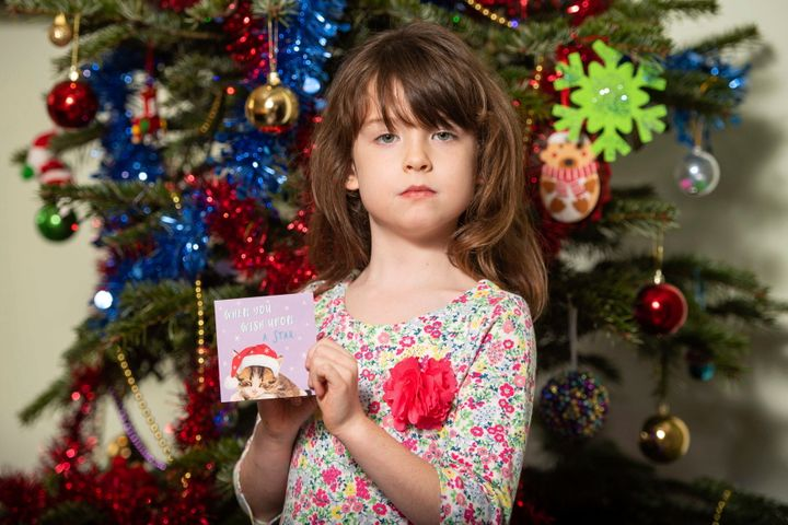 Six-year-old Florence Widdicombe poses Sunday in London with a Tesco Christmas card from the same pack as a card she found containing a message believed to be from a prisoner in China.