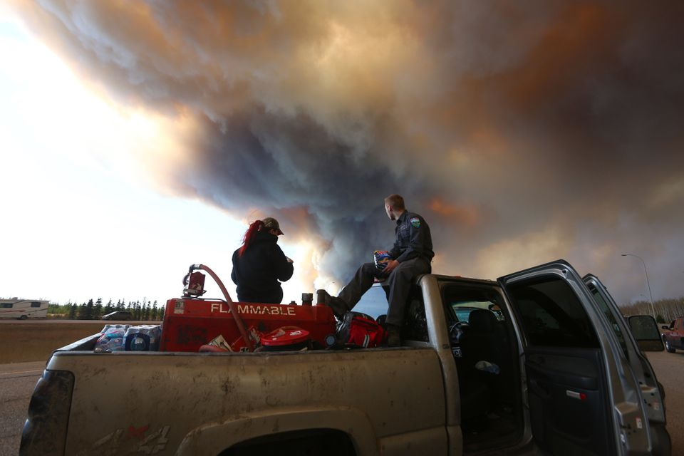 A group trying to rescue animals from Fort McMurray, Alta., wait at a road block as smoke rises from...