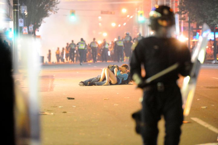 Riot police walk in the street as a couple kiss on June 15, 2011 in Vancouver, Canada.