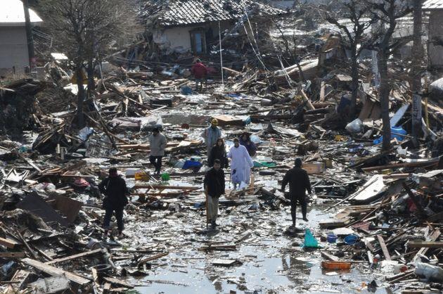 東日本大震災が発生した翌日、がれきの中を歩いて避難する住民=2011年3月12日午前、宮城県名取市。朝日新聞社撮影
