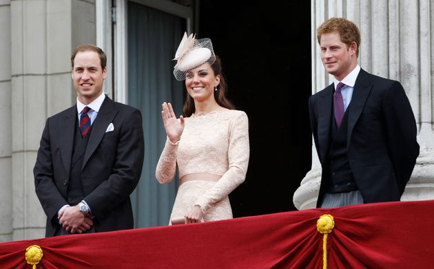 The Duchess of Cambridge waves from the balcony of Buckingham Palace as William and Harry look on, during...