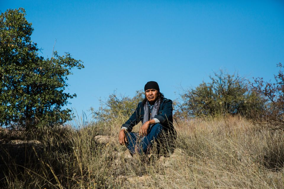 """Wendsler Nosie Sr., 60, sits for a portrait at Chich'il Bildagoteel (Oak Flat) on Nov. 17. The former chairman of the San Carlos Apache Tribe walked 44 miles from Nov. 28 through Dec. 1 from the San Carlos Apache reservation to Oak Flat, where he plans to stay. """"We can all stand up together. We can fix this. We can begin to heal and really develop leaders with a new mission — and that is to protect what's left so that our children will have the opportunity to live,"""" Nosie said. The Nosie-Pikes are enrolled in the San Carlos Apache Tribe, but they're Chiricahua Apache, one of the bands that were imprisoned in the San Carlos reservation after the Apache Wars with the United States in the 1800s."""