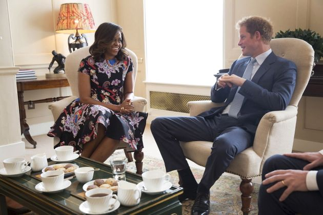 First lady Michelle Obama speaks with Prince Harry during their meeting at Kensington Palace in London...