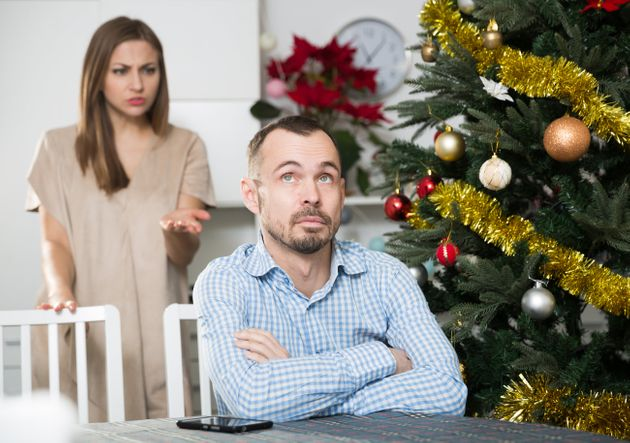 Portrait of adult couple quarreling at home near table with Christmas