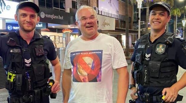 Shawn McCormick with two police officers who liked his T-shirt in Australia's Gold Coast in December
