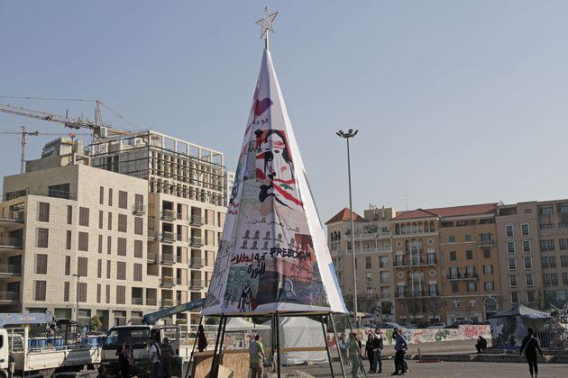 Des manifestants libanais érigent l'arbre de Noël sur la place des Martyrs, le 21