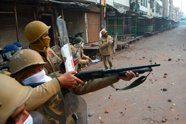 A police personnel aims his gun towards protesters during demonstrations against India's new citizenship...