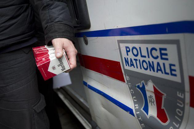 Un policier français tenant des paquets de cigarettes achetés en contrebande à des...