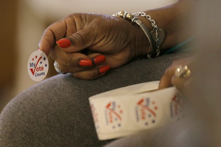 A worker holds stickers for voters at a polling station at the Princeton Baptist Church during the U.S. presidential election