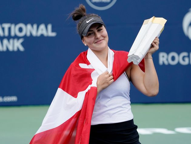 Bianca Andreescu hoists the Rogers Cup trophy after defeating Serena Williams during the Rogers
