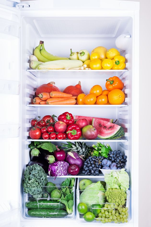 Opened refrigerator full of vegetarian healthy food, vibrant colour vegetables and fruits inside on
