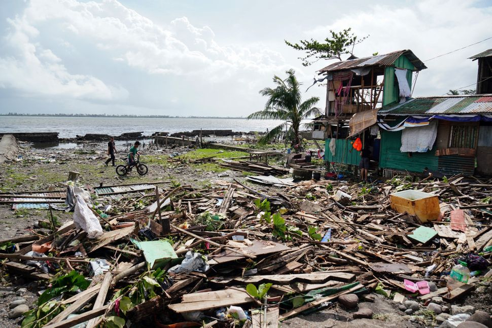 Residents walk past a house damaged during Typhoon Phanfone in Tacloban, Leyte province in the central Philippines on Decembe