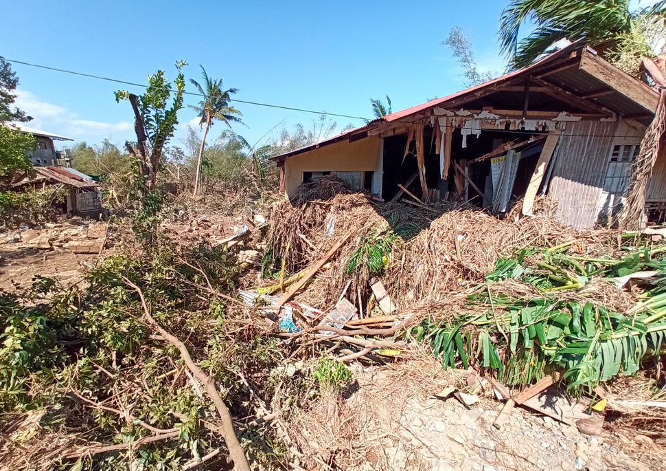 Debris from floods caused by Typhoon Phanfone surround a damaged house in Balasan Town, Iloilo province, central Philippines.