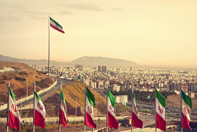 Set of Iran flags in Front of Tehran Skyline and one large flag in the background at sunset with orange...