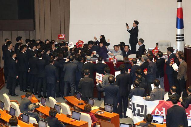 자유한국당 의원들이 27일 서울 여의도 국회 본회의장에서 제373회 국회(임시회) 제1차 본회의 개의를 막기위해 의장석으로 향하는 문희상 국회의장을 둘러싸고