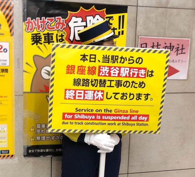 一部区間の終日運休を知らせる看板を持つ係員。溜池山王から渋谷行きの列車は走行しない=12月28日、東京メトロの溜池山王駅