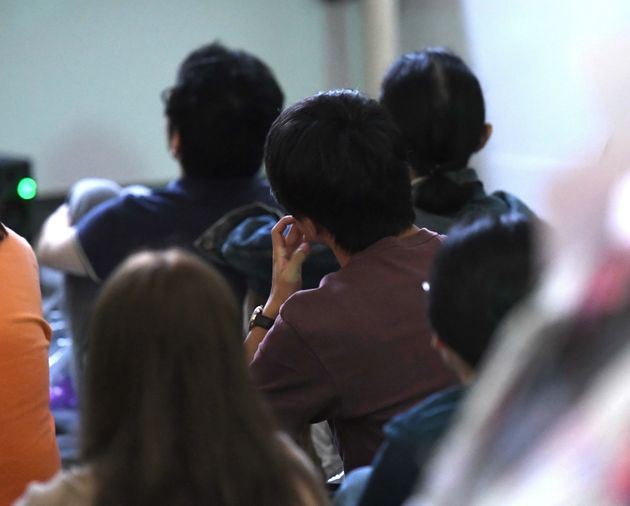 大浦信行さんの昭和天皇をモチーフにした映像作品を観る参加者たち。