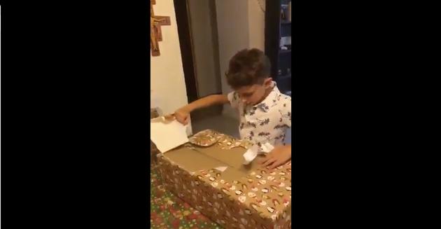 Un niño abre sus regalos de