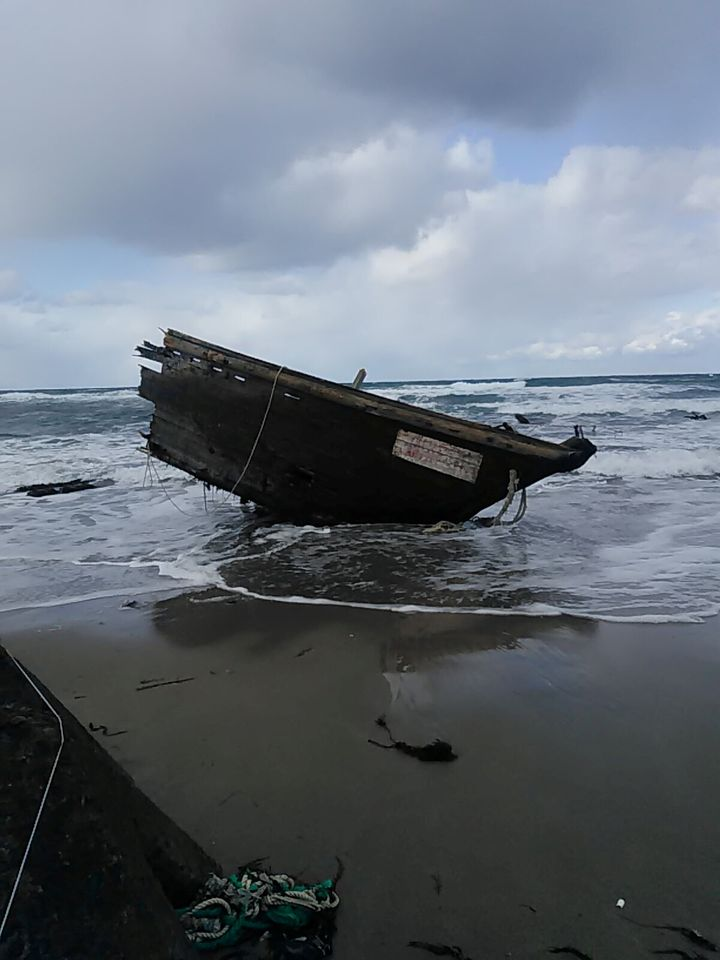 Part of a wooden boat containing human remains and suspected to be from North Korea is seen along a shore of Sado island, Nii