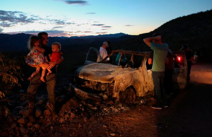 Members of the LeBaron family inspect a burned car where the bodies of nine of their family members were found after an