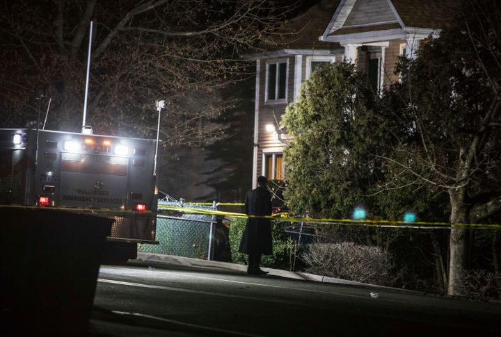 An Orthodox Jewish man stands in front of a residence in Monsey, New York, following a stabbing late Saturday during a Hanukk