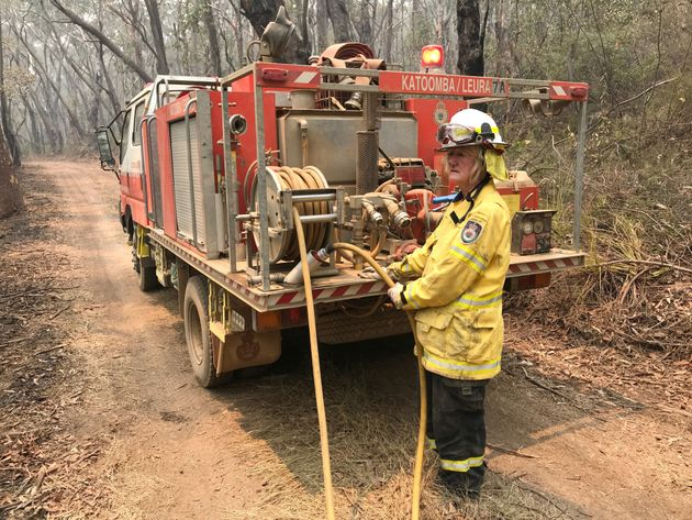 A volunteer from the New South Wales Rural Fire Service works to extinguish spot fires following back...