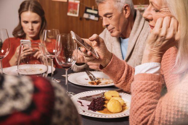 Recreación de una cena navideña con los comensales con expresión de