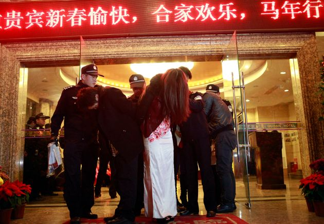 This picture taken late on February 9, 2014 shows Chinese police taking away alleged sex workers and...