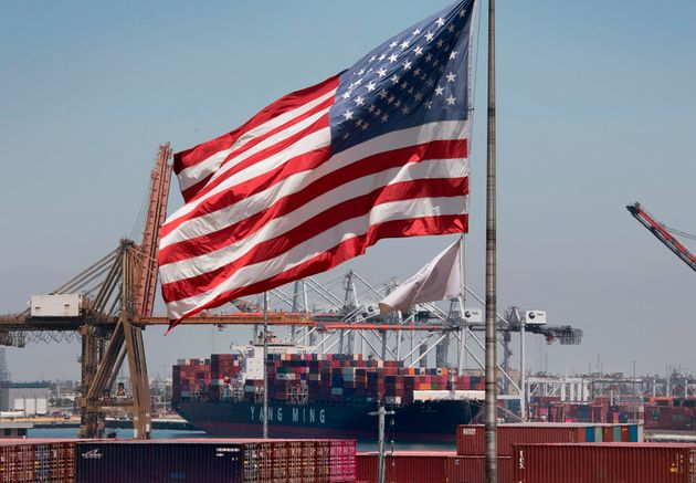 The US flag flies over a container ship unloading it's cargo from Asia, at the Port of Long Beach, California...