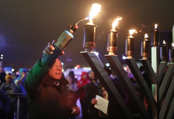 Democratic presidential candidate Sen. Bernie Sanders (I-Vt.) uses a torch to light a menorah during a lighting event at the
