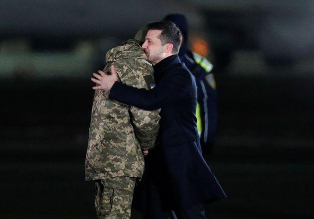 Ukraine's President Volodymyr Zelenskiy greets a Ukrainian serviceman during a ceremony to welcome citizens,...