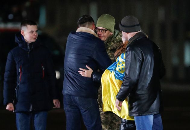 Relatives and acquaintances embrace a Ukrainian serviceman, who was exchanged during a prisoners of war...