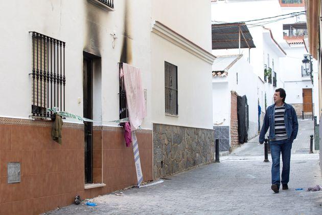 Un hombre pasa por delante de la vivienda donde se registró un incendio en la madrugada de este domingo...