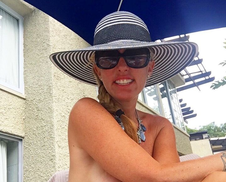Jenny Block wearing just a hat and a necklace while enjoying the sun at a nudist swingers resort.
