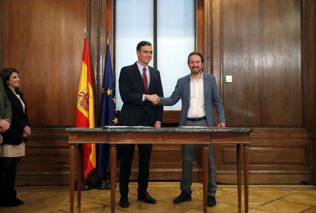 El candidato a la investidura, PedroSánchez (i), y el líder de Podemos, PabloIglesias (d), estrechan...