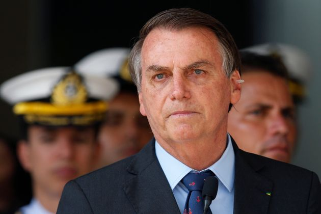 With a bandage on his ear, Brazil's President Jair Bolsonaro attends a military ceremony in honor of...