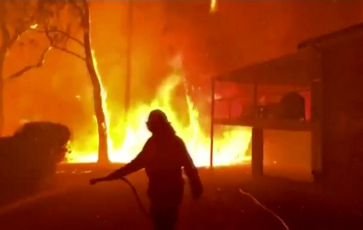 In this image made from video taken and provided by NSW Rural Fire Service via their twitter account, a firefighter sprays water on a fire moving closer to a home in Blackheath, New South Wales state, Australia Sunday, Dec. 22, 2019. Prime Minister Scott Morrison on Sunday apologized for taking a family vacation in Hawaii as deadly bushfires raged across several states, destroying homes and claiming the lives of two volunteer firefighters.(Twitter@NSWRFS via AP)