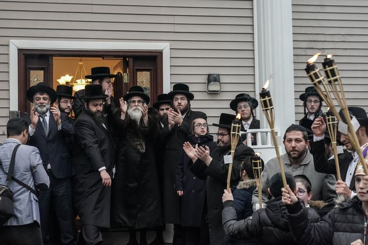 Rabbi Chaim Rottenberg (center left with white beard) celebrates the arrival of a new Torah at his residence in Monsey, New Y