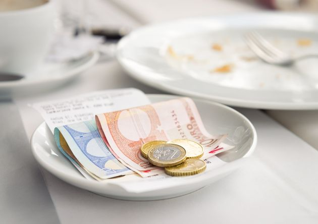 Euro notes and coins left on top of the bill at a European restaurant, as payment and a