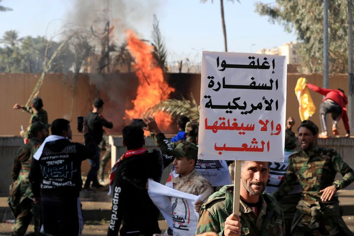 "A Hashd al-Shaabi fighter holds a sign reading ""Close the American embassy otherwise people will close it"" as others set fire"