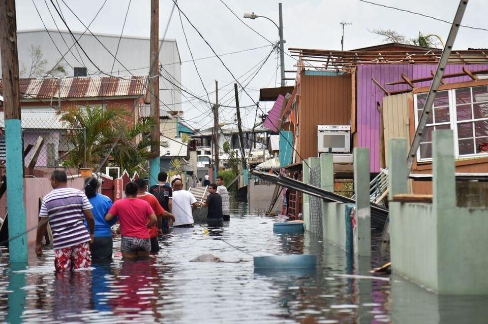 La gente camina por una calle inundada con casas destrozadas en Puerto Rico, el 21 de septiembre de 2017,...