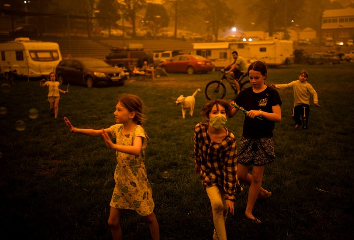 Children play at the showgrounds in the town of Bega where they are camping the fires forced them from their homes.