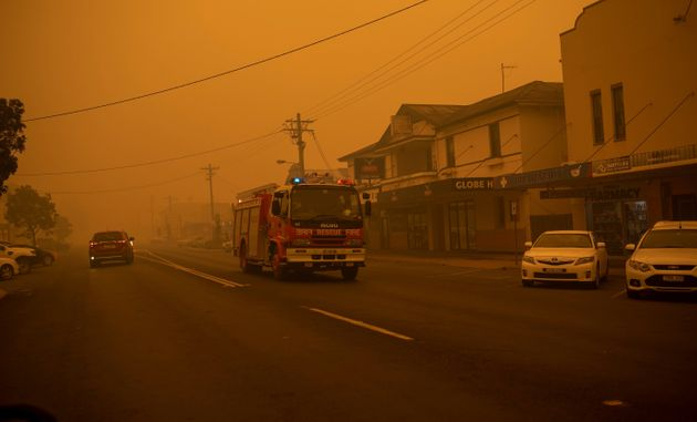 A fire truck moves up the main street of the New South Wales town of Bombala which is shrouded in smoke...